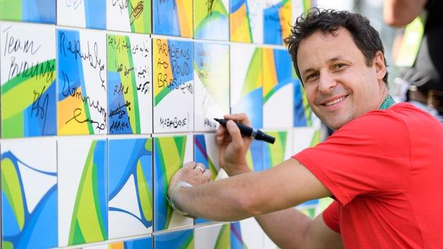 Ralph Stöckli setzt seine Unterschrift auf eine öffentliche Mauer.