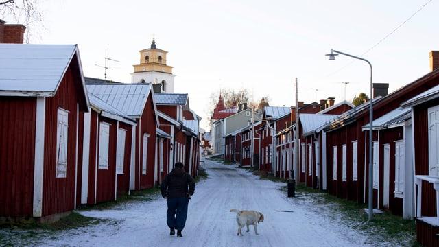 Mann mit Hund auf einem verschneiten Weg, links und rechts rot gestrichene Holzhäuser.