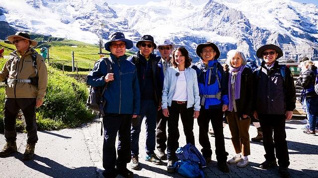 Mona Vetsch mit einer Touristengruppe von verschneiten Bergen