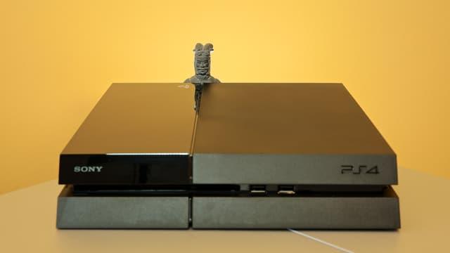 Ein chinesischer Tonkrieger lugt hinter der Playstation 4 hervor.