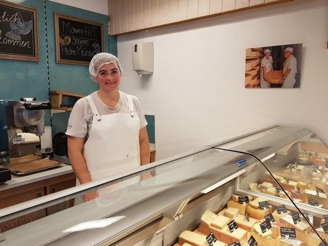 Eine Frau steht hinter der Käsetheke.