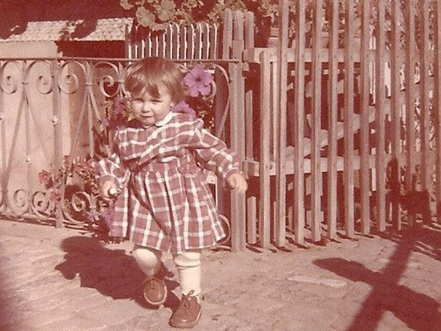 Kleines Mädchen stolziert voller Energie vor einem Gartentor.