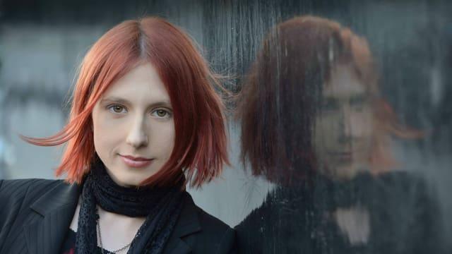 eine junge Frau mit kurzen roten Haaren