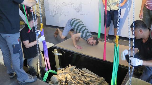 Ein jungsteinzeitliches Grab wird in eine Vertiefung im Boden gelegt.