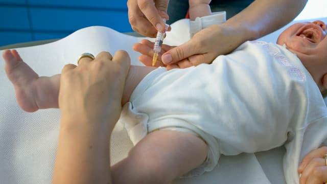 Ein Baby schreit, es erhält gerade eine Spritze in den rechten Oberschenkel.
