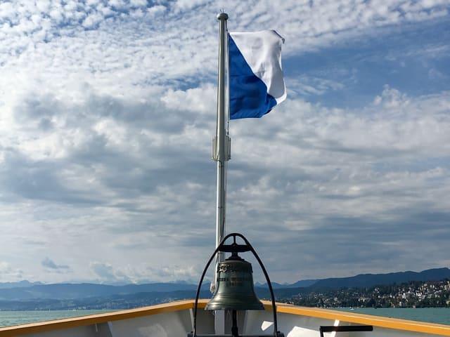 Schiffsbug mit Fahne vom Kanton Zürich in blau/weiss. Der Himmel ist leicht bewölkt und die Sonne scheint.