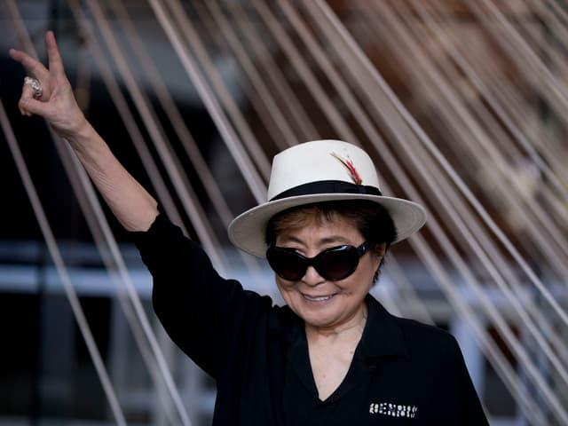 Yoko Ono strekt 2016 ihren Arm in die Luft. die Hand formt ein Peace Zeichen.