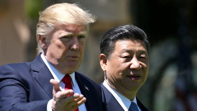 Trump steht neben Xi und gestikuliert.