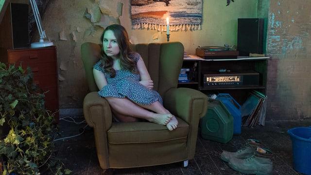 Eine junge Frau sitzt auf einem Sessel. Sie trägt ein blaues Kleid.