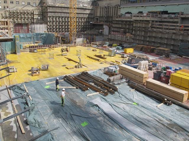 Bauarbeiter auf einer grossen Fläche.