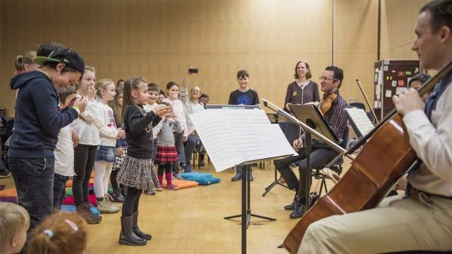 Kinder proben mit Erwachsenen Musikern in einem Saal.