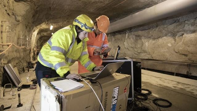 Zwei Forscher im Tunnel schauen auf einen Laptop.