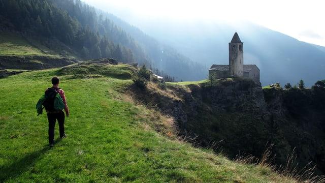 Ein Mann spaziert über eine Wiese, im Hintergrund sieht man einen Wald und eine Kapelle.