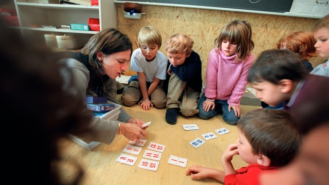 Eine Grundstufe lässt sich von der Lehrerin die Zahlen erklären.