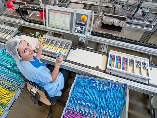 Eine Mitarbeiterin sitz an einem Fliessband und hält einige Zahbürsten in die Luft. Sie trägt ein Haarnetz und einen hellblauen Anzug.
