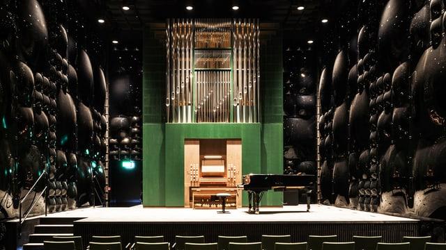 Dunkler, leerer Saal mit einem Flügel und einer Orgel.