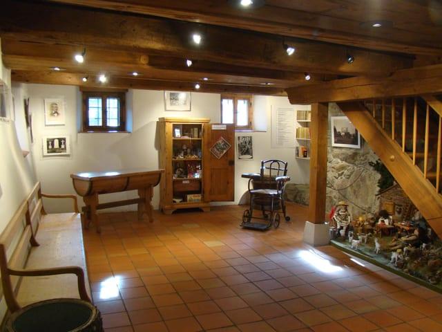 Eine Bank, ein Plattenboden, ein Büchergestell, rechts eine Treppe.