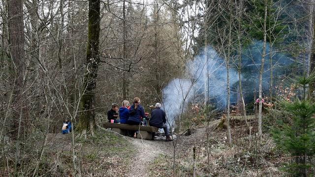 Eine Familie sitzt an einer Grillstelle im Wald
