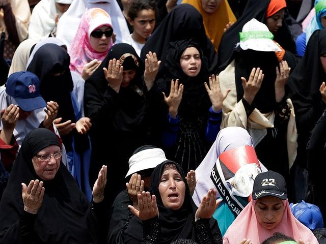 Frauen halten während dem Gebet die Arme in die Höhe