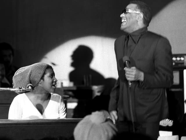 Aretha Franklin am Klavier, daneben steht Ray Charles mit Mikrofon.