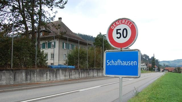 Ortsschild Schafhausen, dahinter das Schulhaus