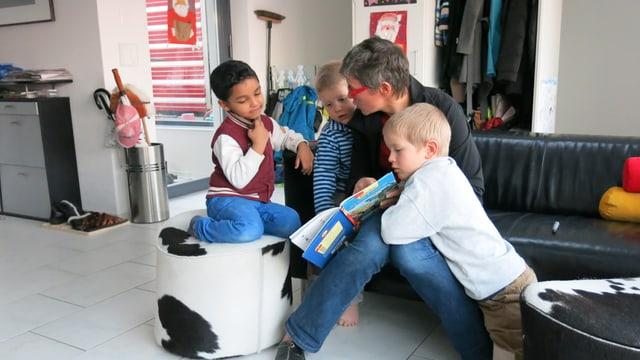 Eine Frau erzählt drei Kindern eine Geschichte, vor sich hält sie ein Buch.