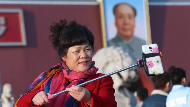 Eine Frau macht ein Selfie von sich und einem Bild von Mao Zedong.