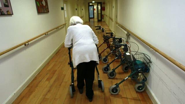 Eine alte Frau geht mit Rollator einen Gang entlang (fotografiert von hinten), zahlreiche weitere Rollatoren stehen herum.