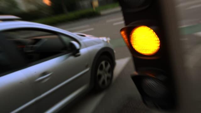 Ein Auto fährt über ein oranges Lichtsignal.