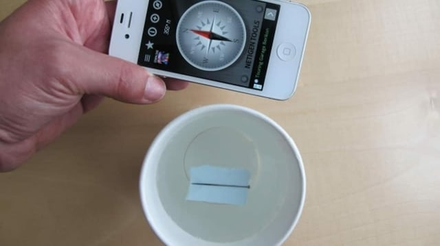 Kompass-Experiment: Wasserschale mit einem Papier drin, Handy mit Kompass als Kontrolle
