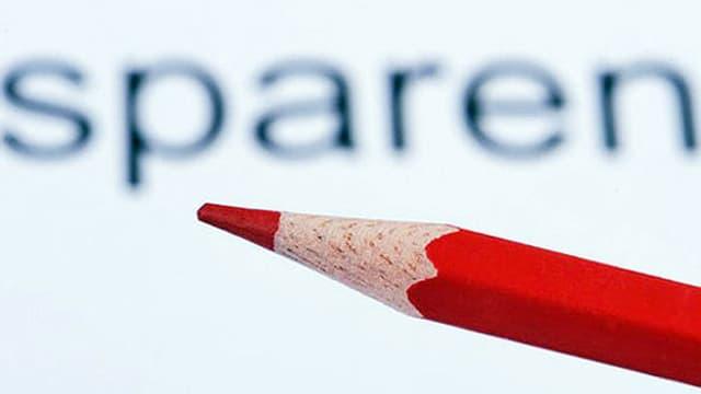Das Wort sparen und ein roter Farbstift.