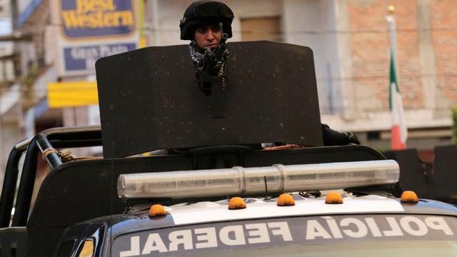 Ein Polizist hinter einem Maschinengewehr, welches auf einem Pickup befestigt ist.
