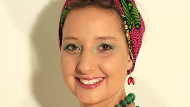 Eine Frau mit farbigem Turban und eine grünen Perlenkette.