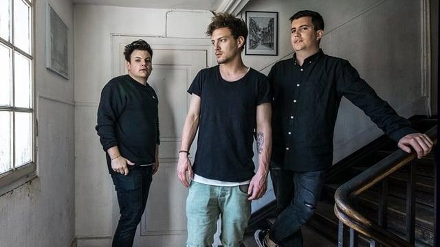 drei junge männer stehn ine inem treppenhaus uns shen wütend aus