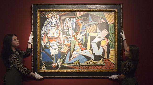 Zwei Frauen halten mit Handschuhen ein Picasso-Gemälde.