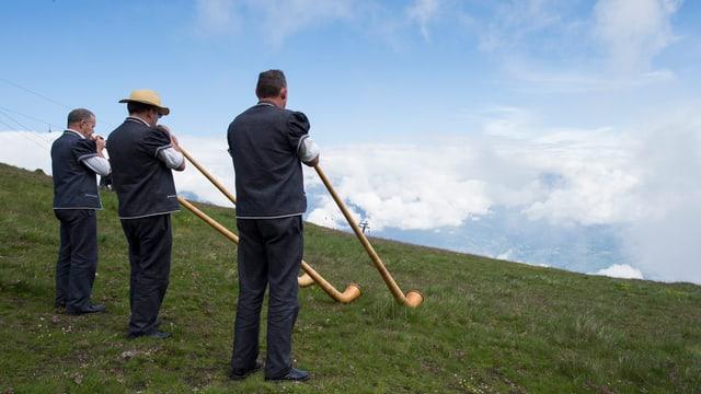 Drei Männer auf einer Alp spielen Alphorn