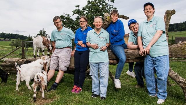Gruppenbild aller sechs Teilnehmerinnen und Telnehmer von «Üse Buurehof» und drei Ziegen. Sie stehen alle vor einem agebrochenen Baustamm.