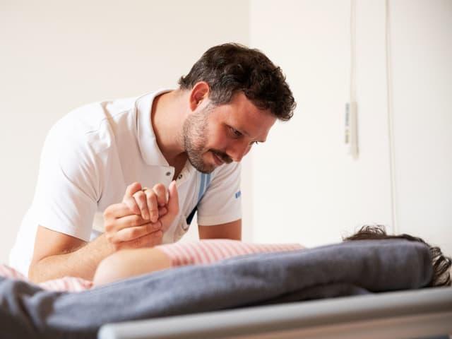 Christof Meiser hält die Hand einer Frau, die auf dem Bett liegt