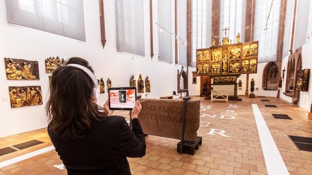 Frau betrachtet ein Kirchenschiff und hält dabei ein Tablet hoch.