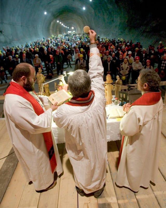 Drei Priester stehen im Tunnel, einer hält eine Hostie hoch.