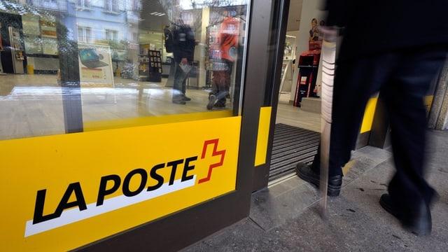 Mann geht durch die Eingangstüre einer Postfiliale.