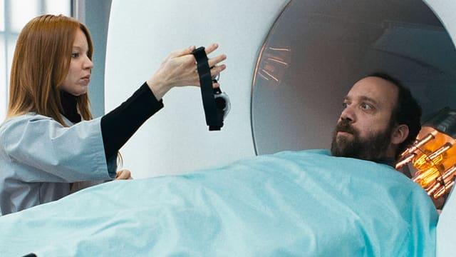 Ein Mann liegt auf einer Liege vor einer Röhre, eine Frau hält ein Gerät vor sein Gesicht.