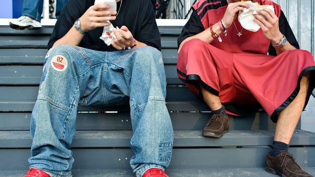 Zwei Jugendliche auf Treppe bei Fastfood-Essen. Unterschiedliche Kleiderstil.