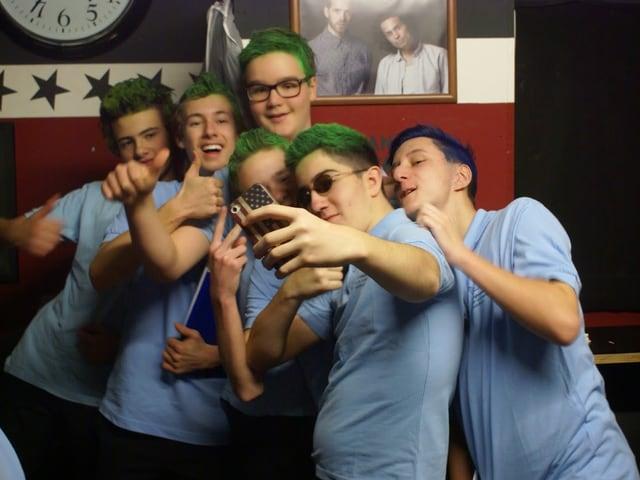 Mehrere Jungs posieren für ein Selfie mit ihren grün gefärbten Haaren.