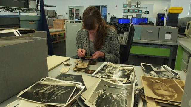 Frau am Schreibtisch schaut Fotos an.