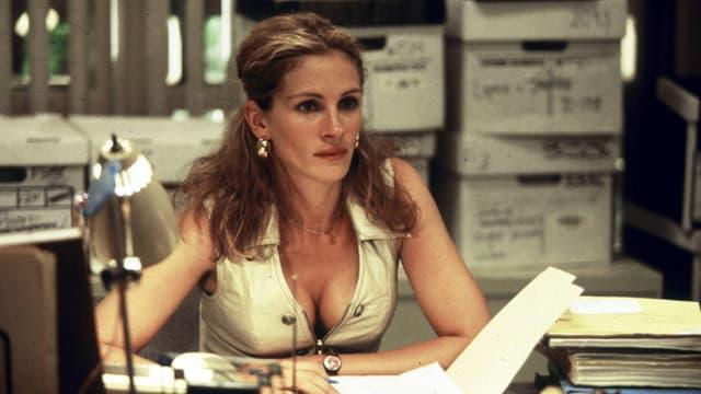 """Bild aus dem Film """"Erin Brockovich"""": Julia Roberts sitzt an einem Schreibtisch zwischen einem Haufen Akten und schaut nachdenklich in die Ferne."""