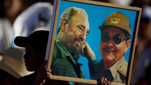 Ein Junge hält ein Bild der Castros.