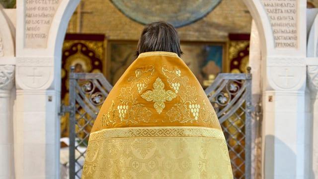Orthodoxer Priester vor einem Altar