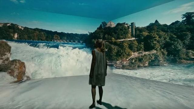 Eine Frau steht in einem Raum, auf dessen Wand der Rheinfall projiziert wird.