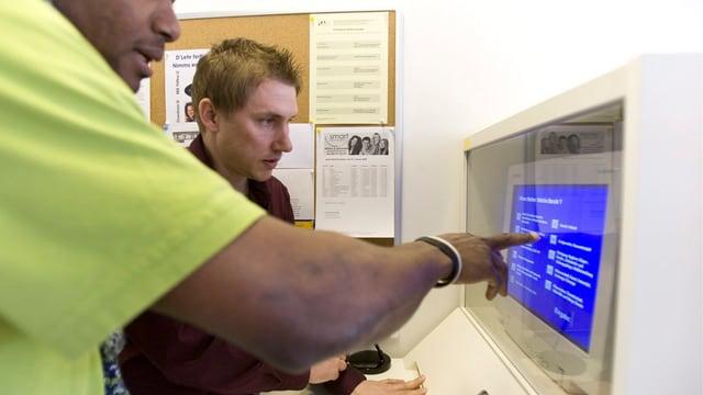 Zwei Männer stehen vor einem Computer.
